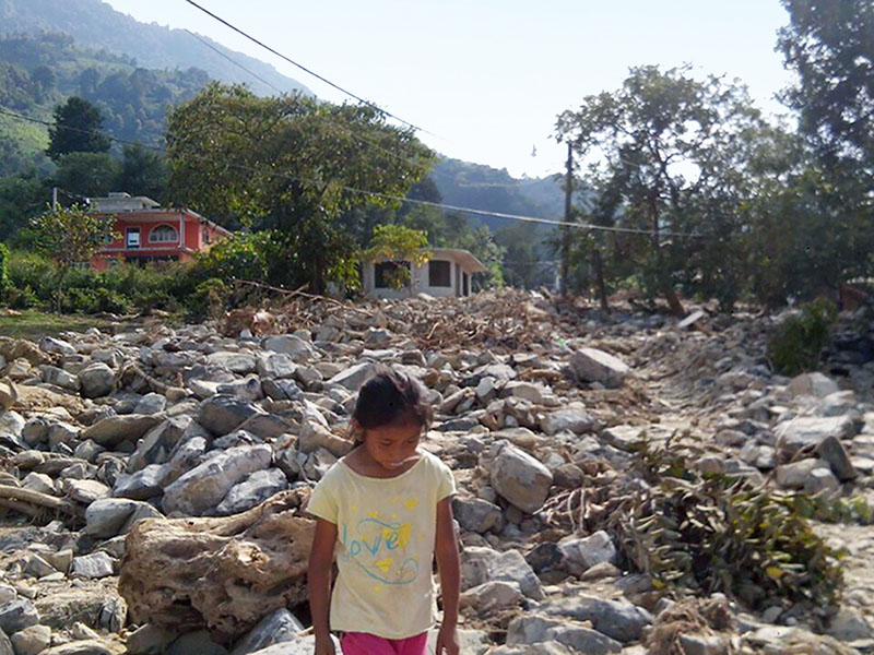 Girl walking through landslide remains from Tropical Storm Earl