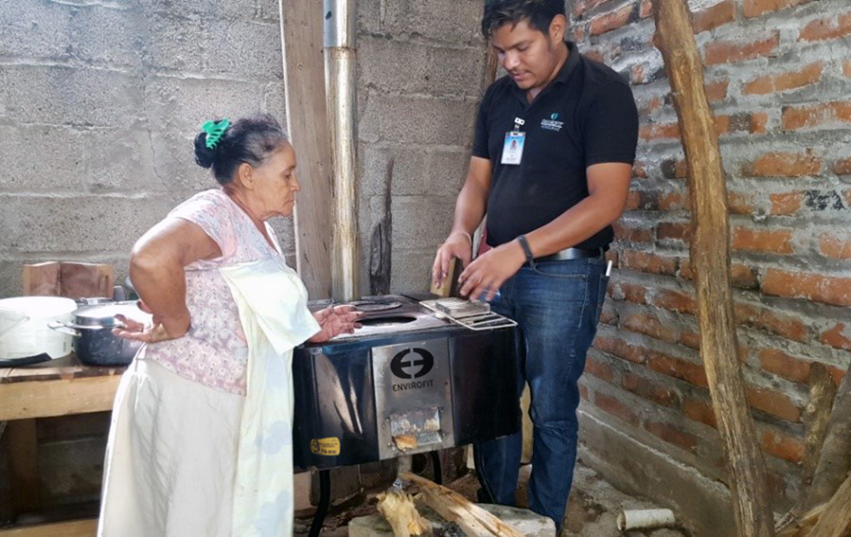 A stove owner talks with an Envirofit Customer Care field team member during an in-home visit