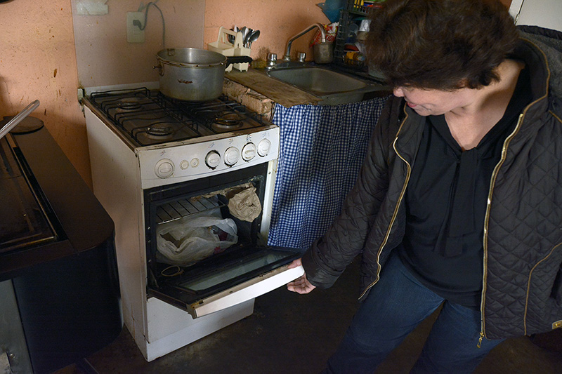 A woman in Mexico uses her LPG stove for storage instead of cooking