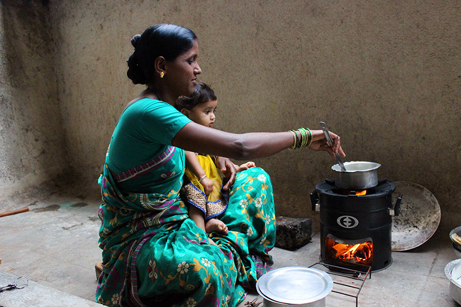A woman and her child sit on a patio cooking with an Envirofit cookstove